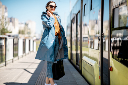Young woman in blue coat waiting for the tram on the station outdoors Фото со стока