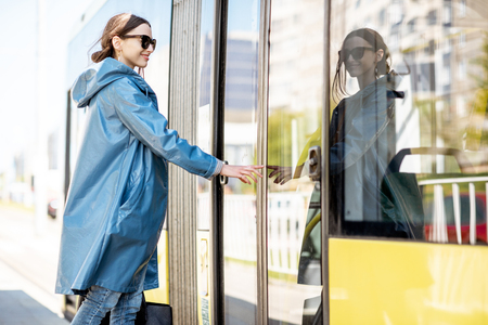 Woman entering the door of the modern tram at the station 写真素材