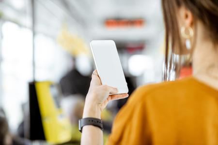 Frau mit Telefon mit leerem Bildschirm zum Kopieren und Einfügen, während sie in der Straßenbahn steht