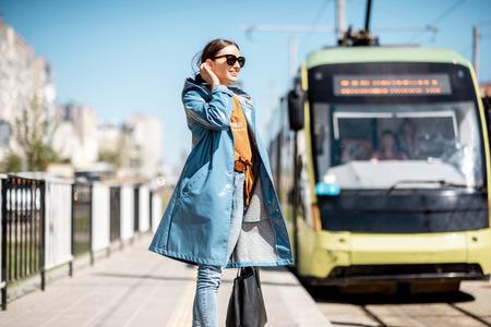 Młoda kobieta w niebieskim płaszczu czeka na tramwaj na dworcu na zewnątrz Zdjęcie Seryjne