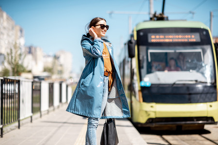 Young woman in blue coat waiting for the tram on the station outdoors