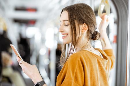 Retrato de primer plano de una mujer joven con smartphone mientras está de pie en el tranvía moderno