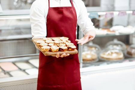 Confectioner holding fresh baked pastels de nata at the pastry shop, close-up Banque d'images