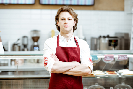 Portrait of a handsome salesman or waiter in red apron standing in the pastry cafe with shop-front on the background