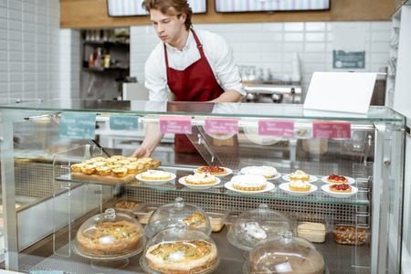 Young salesman in red apron placing sweet pastry in the refrigerator at the showcase of the confectionery shop or cafe