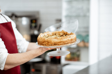 Salesman holding fresh baked pie at the pastry shop, close-up view