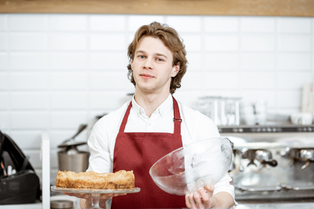 Portrait of a handsome young salesman in red apron standing with fresh pie at the modern pastry shop