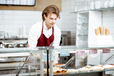 Young salesman in red apron placing sweet pastry in the refrigerator of the showcase at the modern confectionery shop or cafe