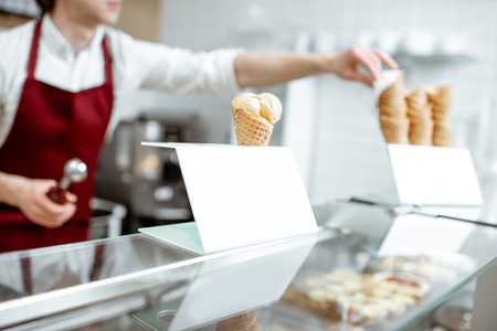 Ice cream in the waffle cone on the counter of the pastry shop with salesperson on the background