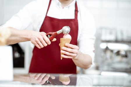 Salesman holding ice cream in the waffle cone and professional scoop on the red apron background, close-up view Foto de archivo - 123036595