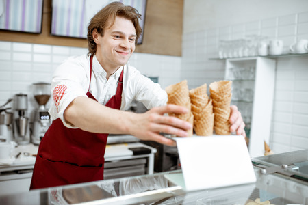 Handsome salesman taking waffle cone while making ice cream for the client in the modern pastry shop