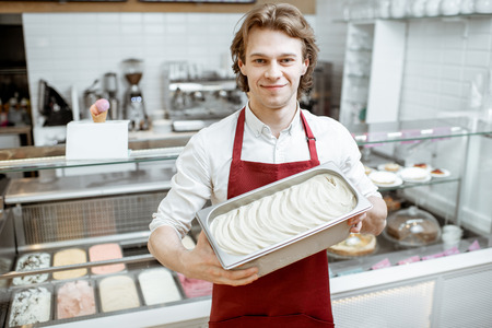 Portrait of a handsome salesman or confectioner in red apron holding tray with ice cream in the shop