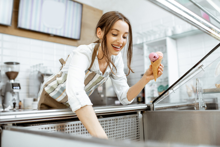 Young and happy saleswoman in apron making ice cream at the counter of the modern pastry shop indoors