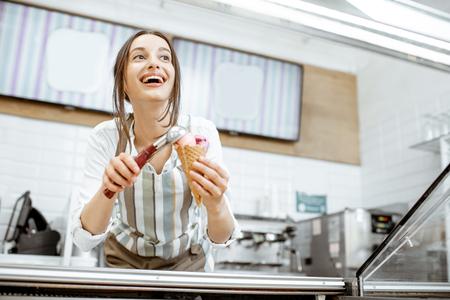 Jeune et heureuse vendeuse en tablier faisant de la crème glacée au comptoir de la pâtisserie moderne à l'intérieur