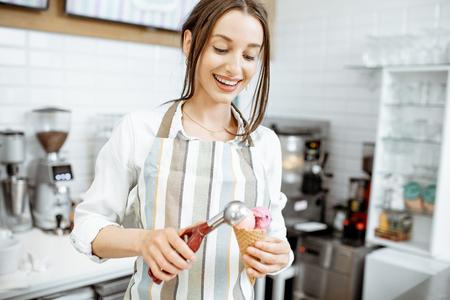 Jeune et heureuse vendeuse en tablier faisant de la crème glacée au comptoir de la pâtisserie moderne à l'intérieur Banque d'images