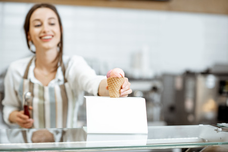 Young and happy saleswoman in apron making ice cream at the counter of the modern pastry shop indoors Banque d'images