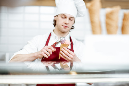 Young salesman in apron and hat making ice cream with waffle cone at the modern pastry shop Foto de archivo - 123036731
