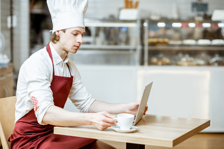 Chef cook in apron and hat working with laptop and drinking coffee in the pastry shop or cafe Zdjęcie Seryjne