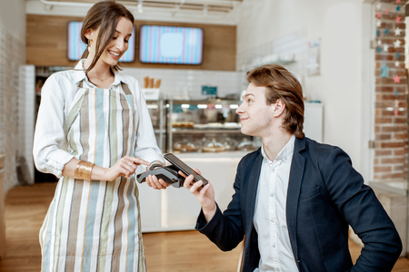 Young businessman with pretty waitress at the cafe, paying contactless with smart phone Stock Photo