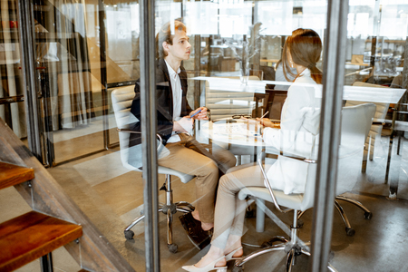 Business man and woman having a conversation in the meeting room, view through the glass partition with reflection Imagens