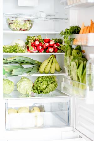 Domestic refrigerator full of fresh vegetables and fruits, carrot, radish, cabbage, lettuce, bananas etc