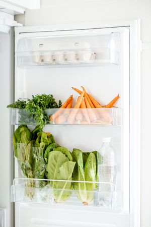 Refrigerators door full of fresh vegetables, carrot, cabbage, lettuce and eggs