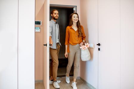 Mooi jong stel dat thuiskomt, samen wandelen in de roze gang van het moderne appartement Stockfoto