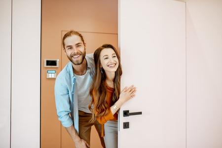 Portret van een jong stel dat de deur uitkijkt op de gang van het nieuwe moderne appartement. Concept van gelukkige eigenaren van onroerend goed