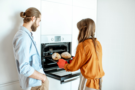 Young and cheerful couple baking breads at the modern white kitchen at home Stock Photo