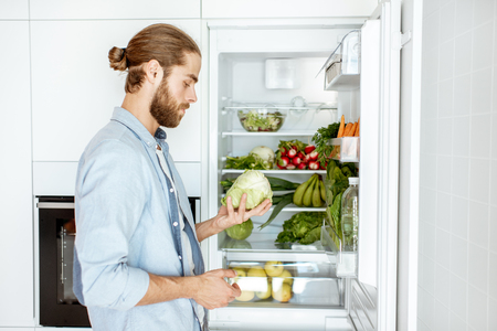 Young vegan man choosing what to cook, taking fresh vegetables from the refrigerator at home Imagens