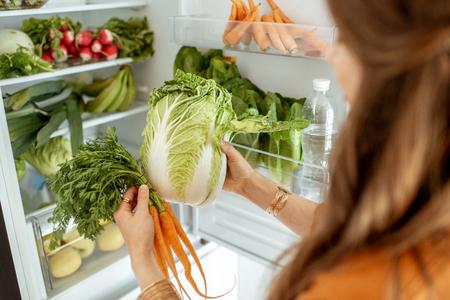 Kobieta biorąca świeżą kapustę i marchewkę z lodówki w domu, widok z bliska