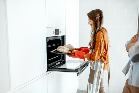 Young and cheerful couple baking breads at the modern white kitchen at home Stockfoto