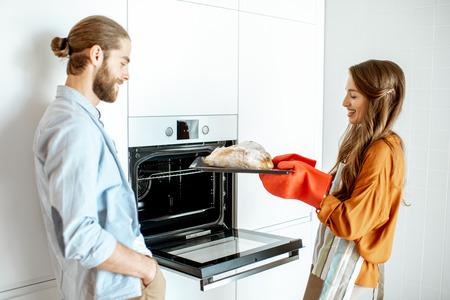 Pareja joven y alegre hornear panes en la moderna cocina blanca en casa Foto de archivo