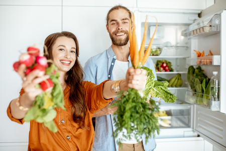 Retrato de una pareja joven y feliz de pie con verduras frescas cerca del refrigerador lleno de productos saludables en casa