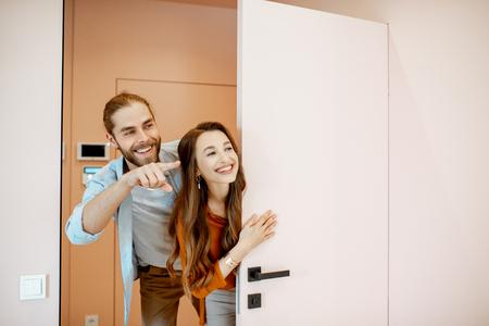 Ritratto di una giovane coppia che guarda fuori dalla porta nel corridoio del nuovo appartamento moderno. Concetto di proprietari immobiliari felici happy