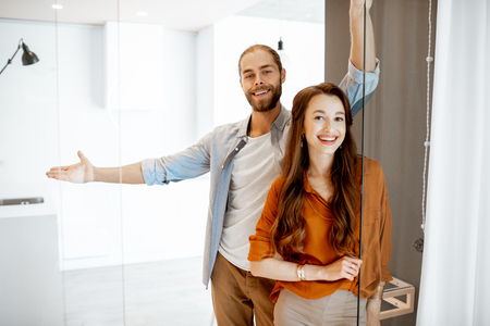 Portrait of a young couple standing together at the new modern studio. Concept of happy real estate owners