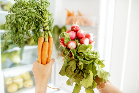 Woman taking fresh radish and carrot from the refrigerator at home, close-up view Stock fotó