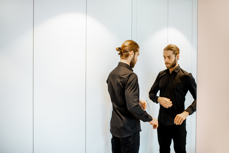 Handsome man wearing black shirt, preparing for the formal event, while standing near the mirror at the wardrobe at home Banco de Imagens