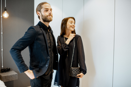 Young couple preparing for the serious event, wearing black formal clothes, standing together at the wardrobe at home