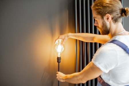 Handyman in uniform replacing lightbulb in the living room at home Stock Photo