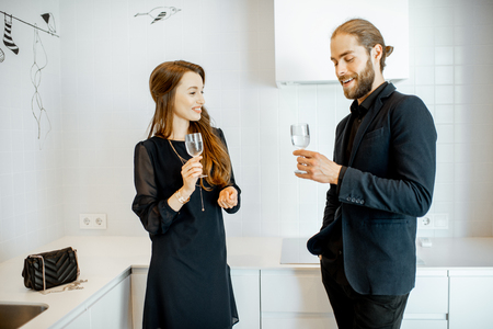 Man and woman in black formal clothes having unofficial meeting with drinks in the kitchen at home