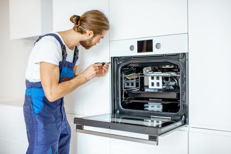 Trabajador guapo en ropa de trabajo instalando horno eléctrico en los estantes de la cocina en la cocina moderna en casa