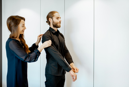 Young couple wearing black formal clothes, preparing for the serious event in the bedroom at home Banco de Imagens