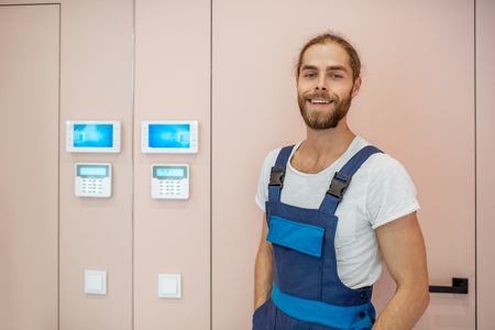 Portrait of an electrician setting up the alarm, standing in the apartment corridor Stock Photo