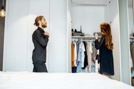 Young couple wearing black formal clothes, preparing for the serious event in the bedroom at home 写真素材