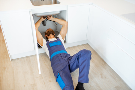 Plumber in overalls repairing or installing sewerage under the kitchen sink at home Reklamní fotografie