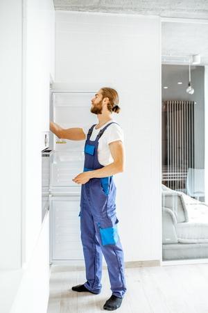 Handsome workman installing new refrigerator in the modern kitchen at home