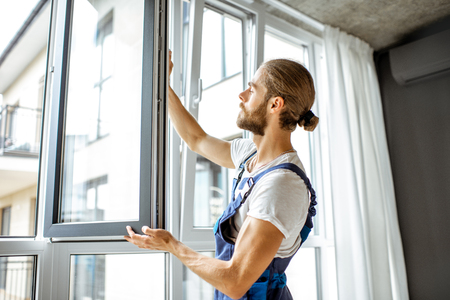 Workman in overalls installing or adjusting plastic windows in the living room at home Stock Photo