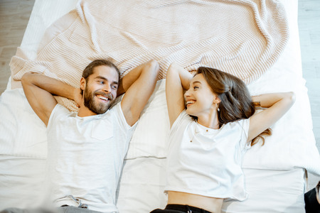 Portrait of a young and cheerful couple lying on the bed, view from above