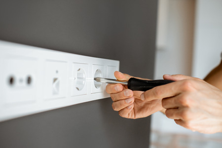 Electrician mounting electric sockets on the grey wall at home